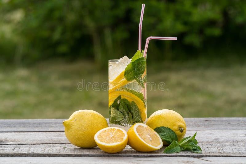 sommar f?r sn?ckskal f?r sand f?r bakgrundsbegreppsram Lemonad med citronen, mintkaramellen och is, i ett exponeringsglas, över d royaltyfri fotografi