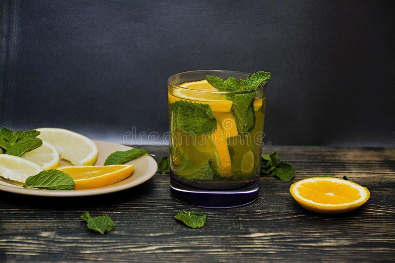 Sommar, f?rnyande orange drink med mintkaramellen och orange skivor m?rkt tr? f?r bakgrund Slapp fokus royaltyfri bild