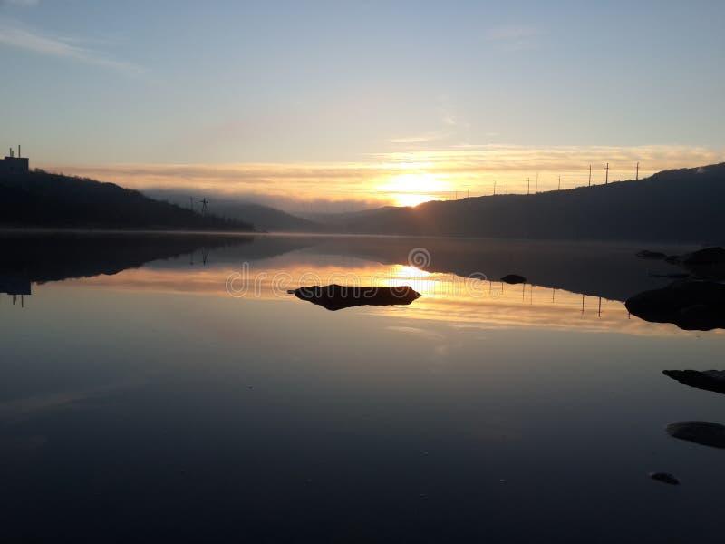 Sommar i den arktiska cirkeln Starten av den mörka tidspunkten, med en underbar utgående sol, på bakgrunden av sjön och Het arkivbild