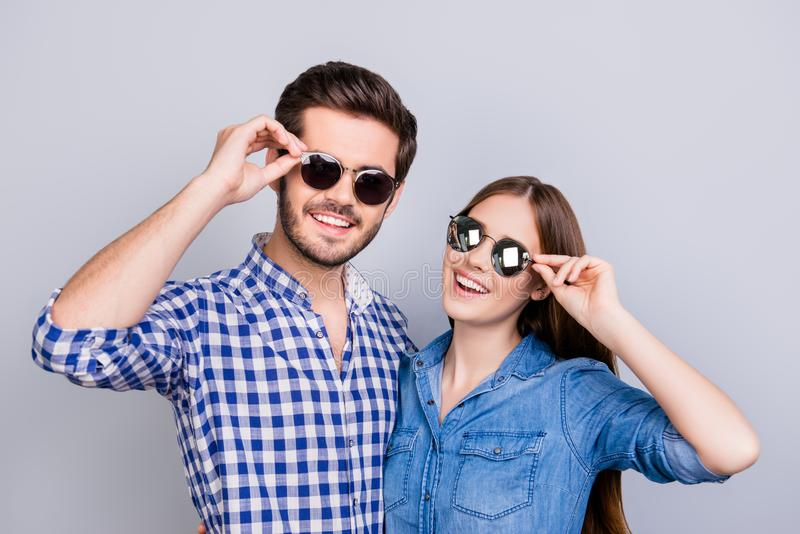 Sommar- och gyckellynne Unga studenter bär moderiktig solglasögon och leende, i tillfälliga skjortor som poserar på den rena bakg royaltyfri bild
