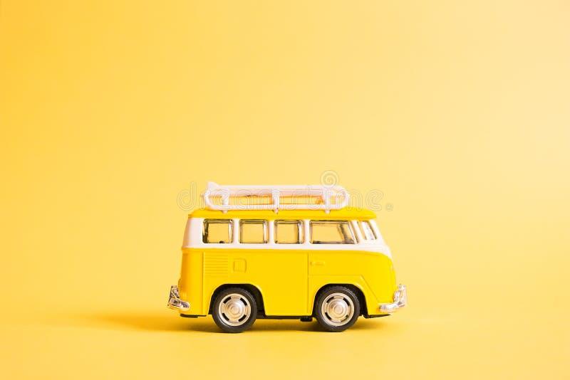 Sommar semestrar affischen med den retro gula bussskåpbilen på gul bakgrund Rolig retro bil med surfingbr?dan barn f?r kvinna f?r arkivfoton