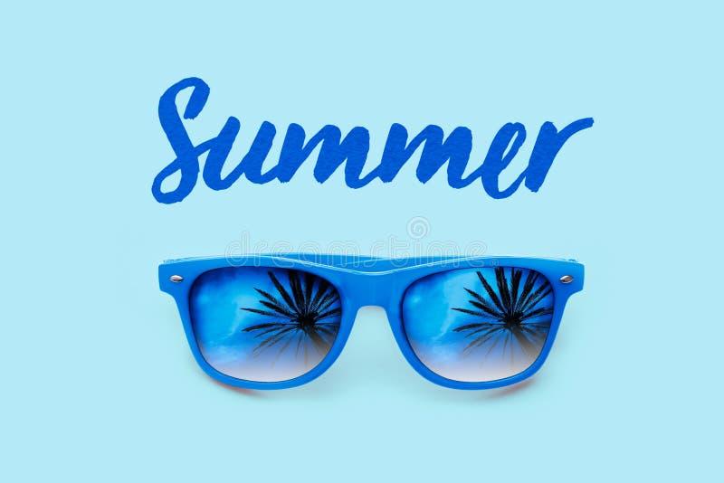 Sommar texturerad blå text och blå solglasögon med palmträdreflexioner som isoleras i ett ljus - blå bakgrund arkivfoto