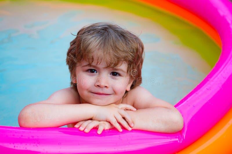 Sommaravkoppling i p?len Ett barn ligger och kopplar av i en hem- pöl med ett leende Sommar vilar semestrar behandla som ett barn royaltyfri bild