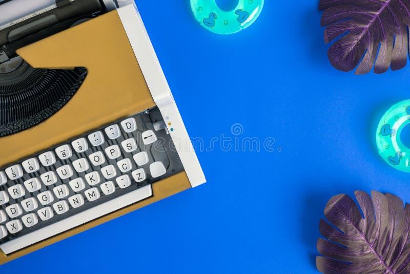Sommarbakgrund gjorde av den gula skrivmaskinen, monsterasidor och uppblåsbara flöten på blått Utrymme för kopierar royaltyfria foton