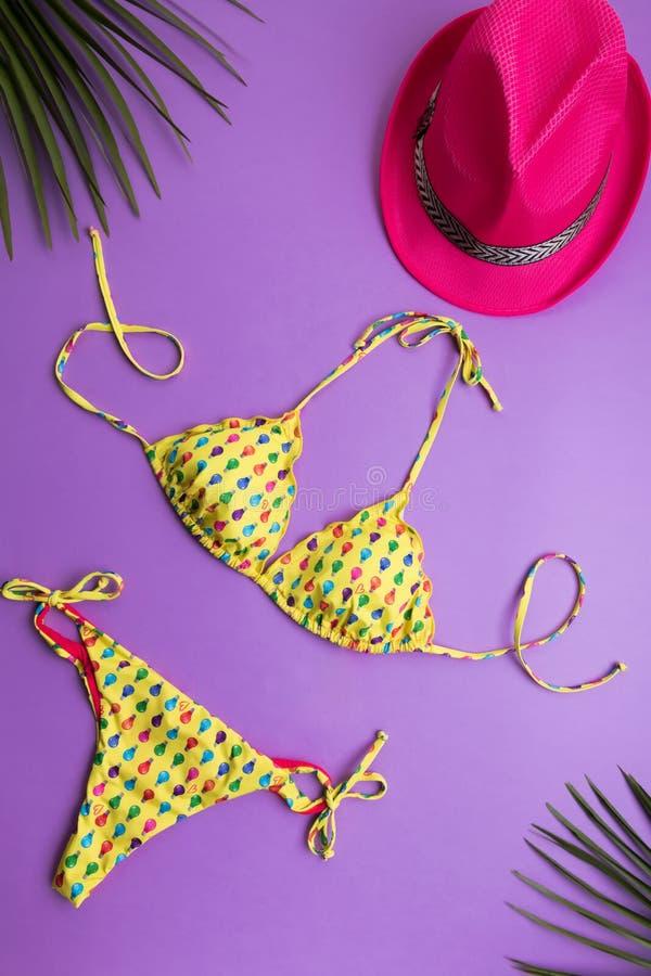 Sommarbakgrund med palmblad, rosa modehatt och bikini på violett eller purpurfärgad bakgrund, lopp och semestrar begrepp, överkan royaltyfri foto