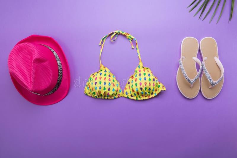 Sommarbakgrund med palmblad, rosa modehatt och bikini på violett eller purpurfärgad bakgrund, lopp och semestrar begrepp, överkan fotografering för bildbyråer