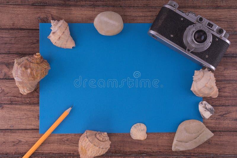 Sommarbakgrunds-begrepp av sommarferier på den tropiska stranden retro kamera med snäckskal från havet på en trätabell arkivbild