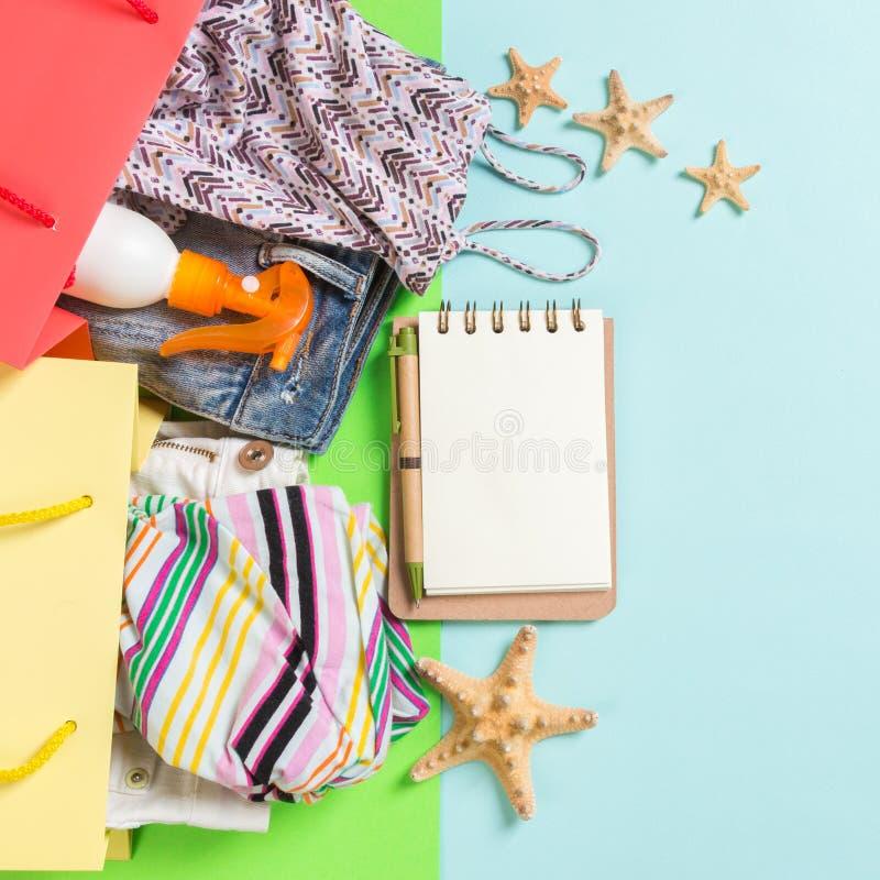 Sommarbegrepp av färgglade shoppa påsar som är fulla av kläder Gåvapåsar med T-tröja, grov bomullstvillkortslutningar, anteckning arkivfoto
