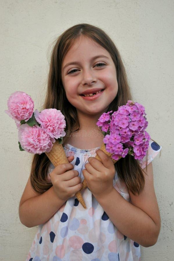 Sommarbegrepp med unga flickan som äter en blommakotte royaltyfri foto