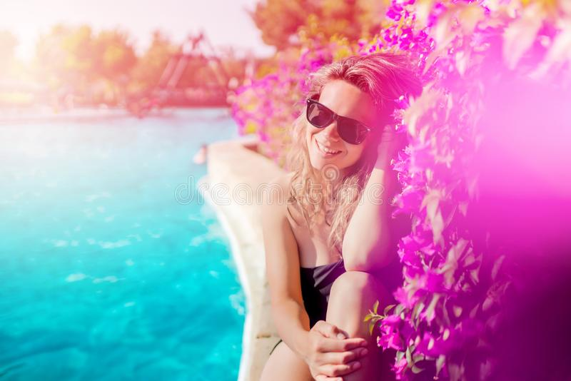 Sommarbegrepp - sexig kvinna som kopplar av nära simbassäng, le och bärande solglasögon för poolside arkivbild