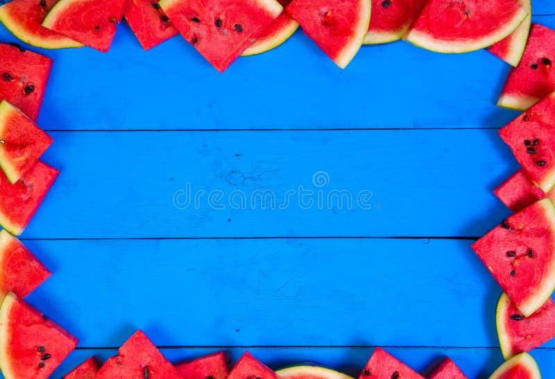 Sommarbegrepp: Skivad vattenmelon på blå lantlig wood bakgrund arkivfoto
