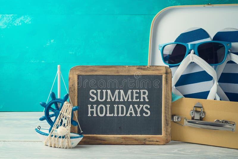 Sommarbegreppsbakgrund med gulligt roligt bläddrar det misslyckande-, resväska- och svart tavlatecknet arkivfoton
