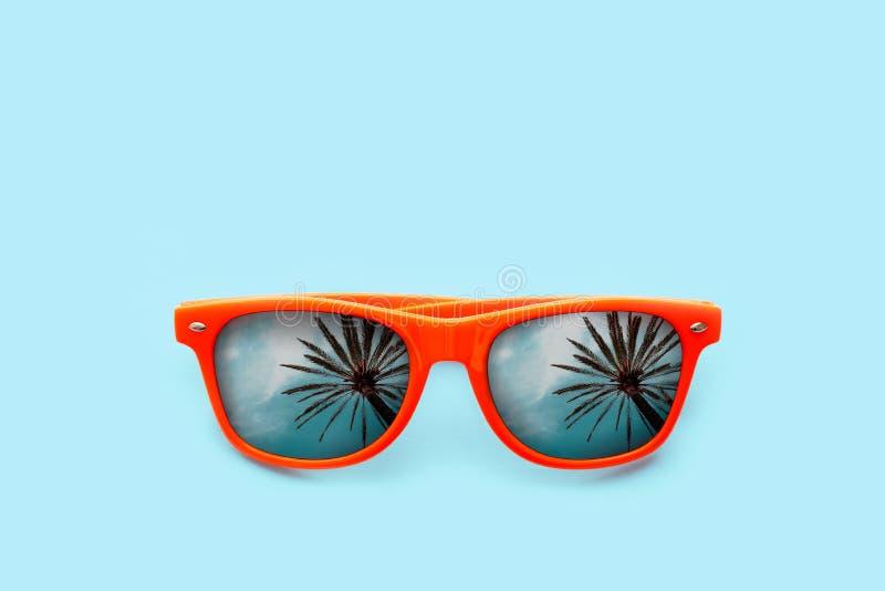 Sommarbegreppsbild: den orange solglasögon med palmträdreflexioner i pastell slösar bakgrund royaltyfri bild