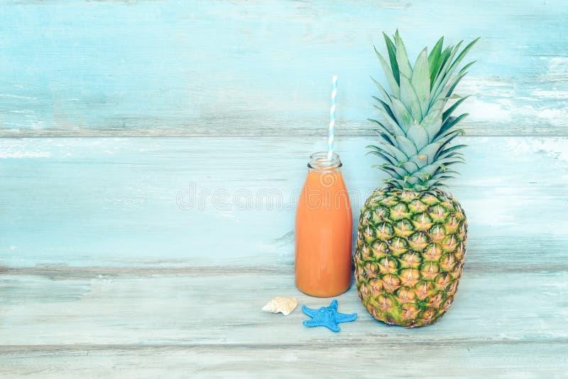 Sommarbegreppsstillife - mogen ananas och en flaska av multivitaminfruktsaft framme av en blå lantlig träbakgrund arkivbild