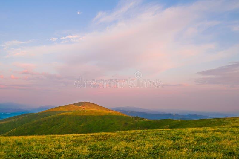 Sommarberglandskap: bergöverkanten glöder med ljus på royaltyfria bilder