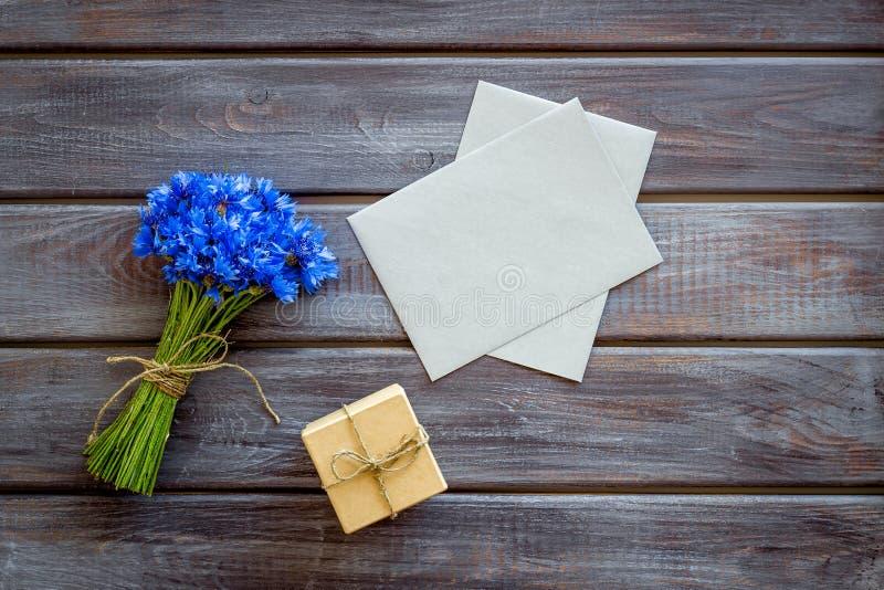 Sommarblommamodell med buketten av den blåa blåklinter, kuvert och gåvan i ask på träåtlöje för bästa sikt för bakgrund upp arkivfoton