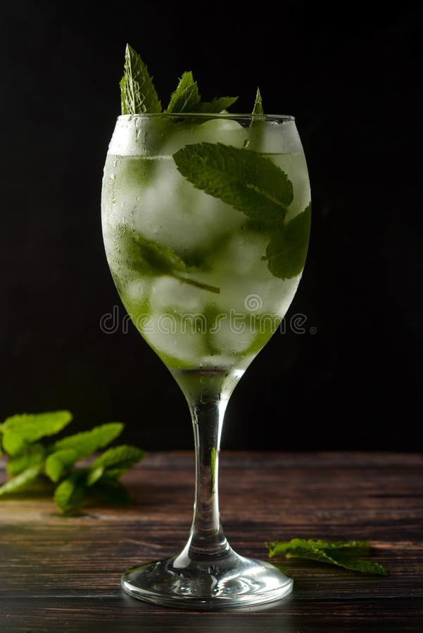 Sommarcoctail eller drink i vinexponeringsglas Förnyande drink med mintkaramellsidor, ginuppiggningsmedel, syrop M?rkt foto arkivfoton