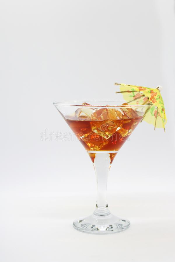 Sommarcoctail i ett exponeringsglas med is och ett paraply royaltyfri bild