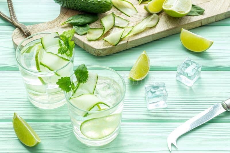 Sommarcoctailar för friskhet med limefrukt, gurkan och is på mintkaramellgräsplanträbakgrund fotografering för bildbyråer