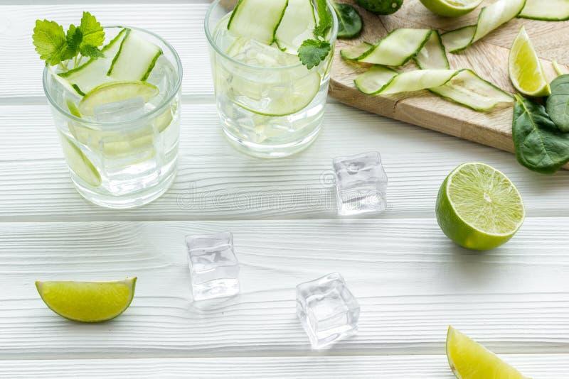 Sommarcoctailar för friskhet med limefrukt, gurkan och is på träbakgrund royaltyfria bilder
