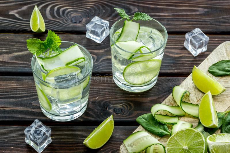 Sommarcoctailar för friskhet med limefrukt, gurkan och is på träbakgrund fotografering för bildbyråer