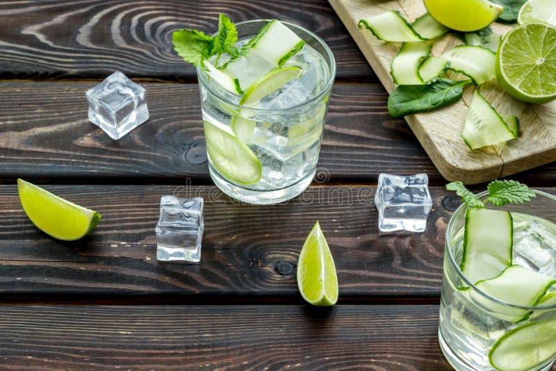 Sommarcoctailar för friskhet med limefrukt, mintkaramellen, gurkan och spenat på träbakgrund royaltyfri fotografi