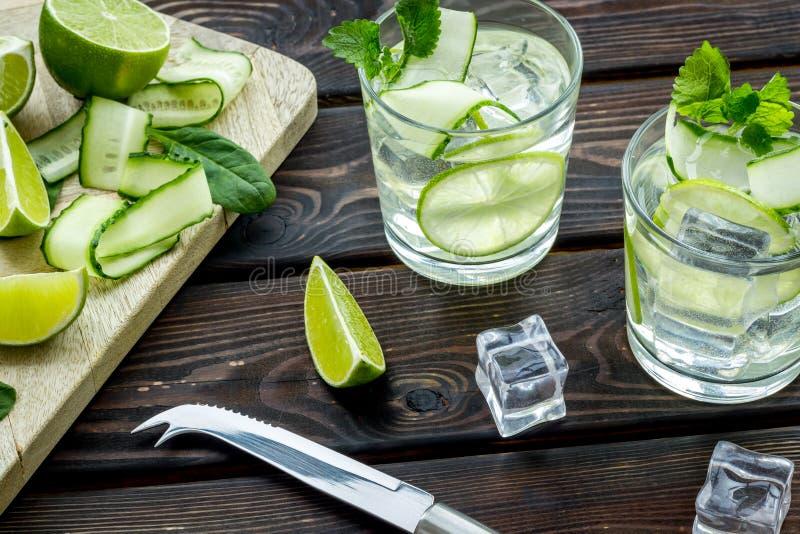 Sommarcoctailar f?r friskhet med limefrukt, gurkan och is p? tr?bakgrund fotografering för bildbyråer