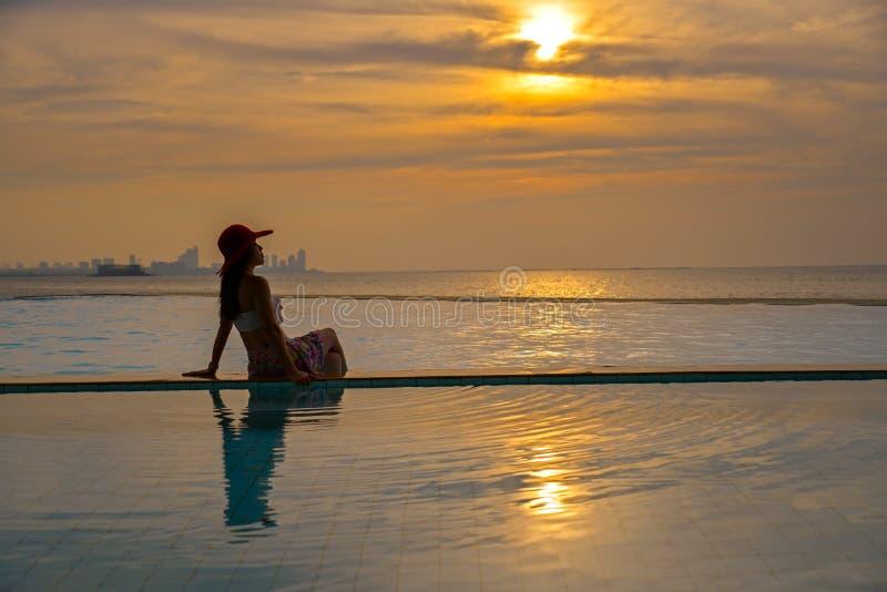 Sommardag, asiatisk ung kvinna som är lycklig i den stora hatten som kopplar av på simbassängen, lopp nära havet och strand i sol arkivfoto