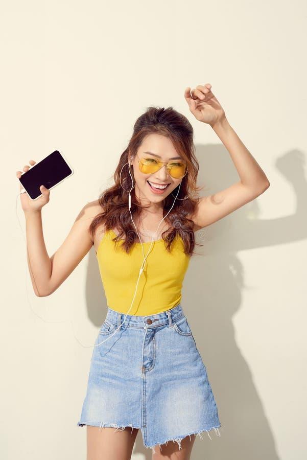 Sommardam Härlig asiatisk flicka med yrkesmässig makeup och stilfullt frisyrsjunga och dans, medan lyssna till musik på arkivfoton