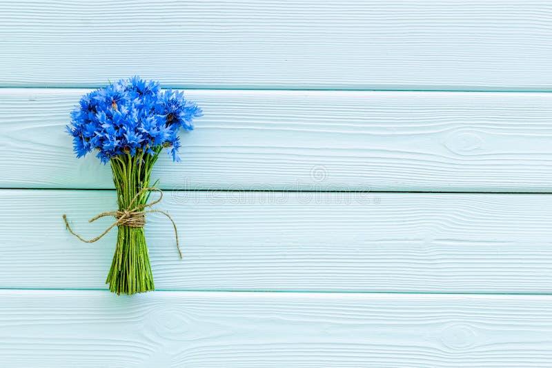 Sommardesign för blogg med buketten av blåa blåklinter på copyspace för bästa sikt för mintkaramellgräsplanträbakgrund arkivfoto