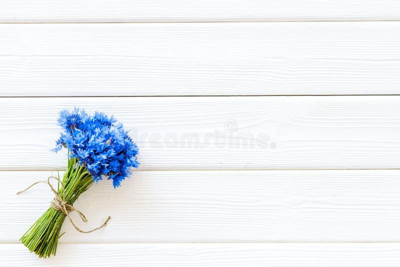 Sommardesign för blogg med buketten av blåa blåklinter på vit träcopyspace för bästa sikt för bakgrund royaltyfri foto