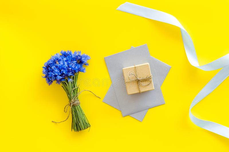 Sommardesign för blogg med buketten av det blåa blåklinter, kuvertet och gåvan på bästa sikt för gul bakgrund royaltyfria bilder