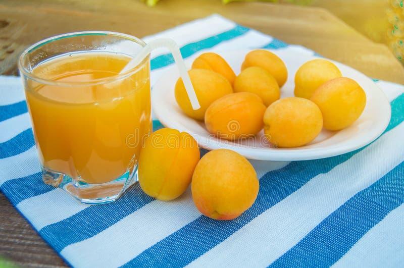 Sommardrink och frukt-ny aprikosfruktsaft i en exponeringsglasexponeringsglaskopp med ett sugr?r och mogna aprikors p? en servett royaltyfri foto