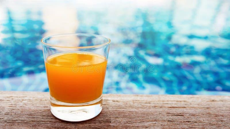 Sommardrink på simbassängen Exponeringsglas av orange fruktsaft på arkivbilder