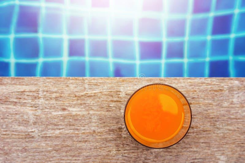 Sommardrink på simbassängen Exponeringsglas av orange fruktsaft på arkivbild