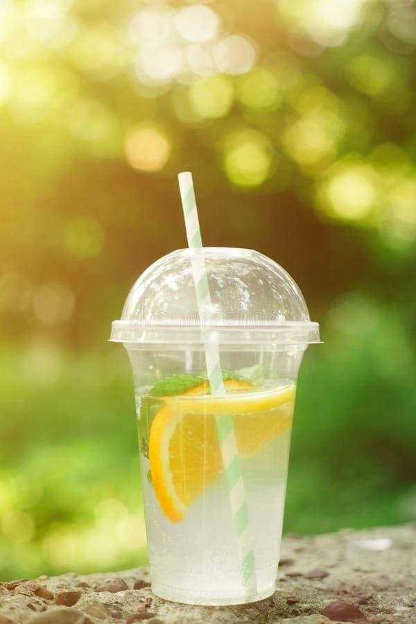 Sommardrinklemonad med apelsinen och mintkaramellen i den plast- koppen mot livlig gr?n bakgrund arkivbilder