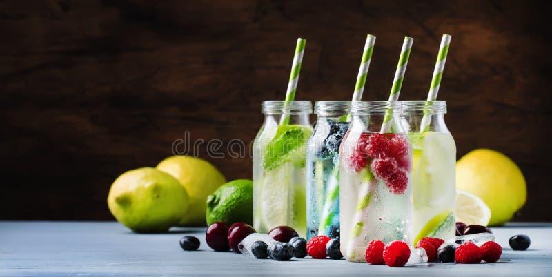 sommardrinkupps?ttning Bär, frukt och citrus icke-alkoholist som förnyar iskalla drycker och coctailar i glasflaskor på blått royaltyfri fotografi
