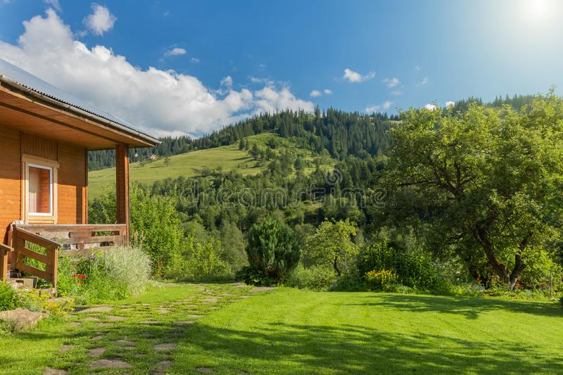 SOMMAREN landskap Trähus med en sikt av de Carpathian bergen arkivbilder