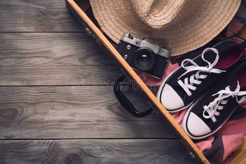Sommarferier och semesterloppbegrepp Tappningkamera, sugrörhatt och gymnastikskor i gammal resväska på träbakgrund Top beskådar arkivfoto