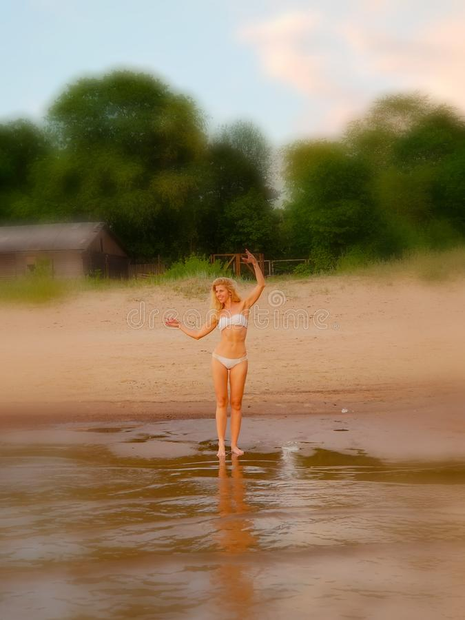Sommarferier, semester och strandbegrepp - blond flicka i den vita bikinin som poserar p? stranden bakgrundsblurblomma inom som l royaltyfria bilder