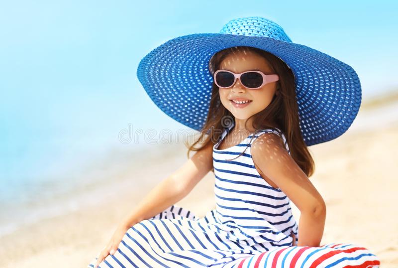 Sommarferier, semesterbegrepp - härlig liten flicka för stående i sugrörhatten, randig klänning som kopplar av på stranden royaltyfria bilder