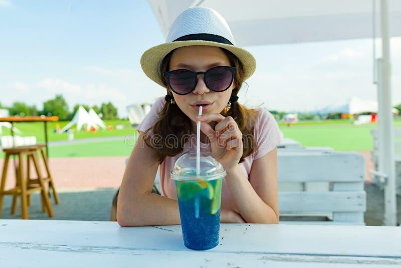 Sommarferier, vilar den tonårs- flickan av 14 år i hatt, och solglasögon med blå lemonad sitter på tabellen i sommargatakafé _ fotografering för bildbyråer