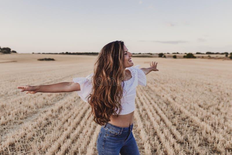 Sommarflicka som tycker om naturen på gult fält Härlig ung kvinna som utomhus dansar Långt hår i vinden Lycka och royaltyfria foton