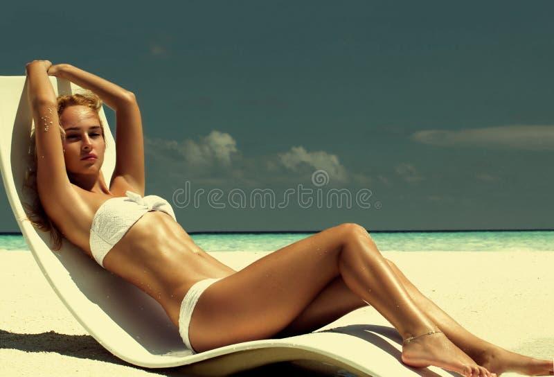 Sommarflickamodell med den brunbrända sexiga kroppen Posera i den vita chaen royaltyfri fotografi
