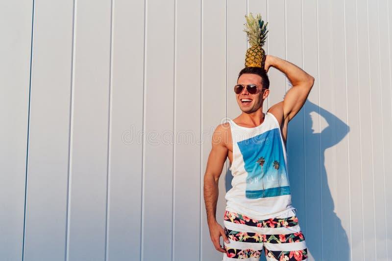 Sommarfoto av den sportive mannen som rymmer en ananas på hans huvud, utomhus royaltyfri foto