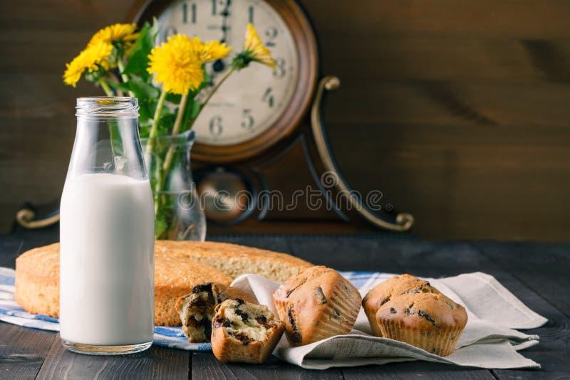 Sommarfrukosten med muffin, mjölkar, och maskrosen blommar arkivbild