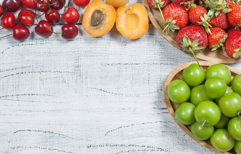 Sommarfrukter, gr?n plommon, r?d k?rsb?r, jordgubbe, aprikos p? vit tr?bakgrund royaltyfri foto