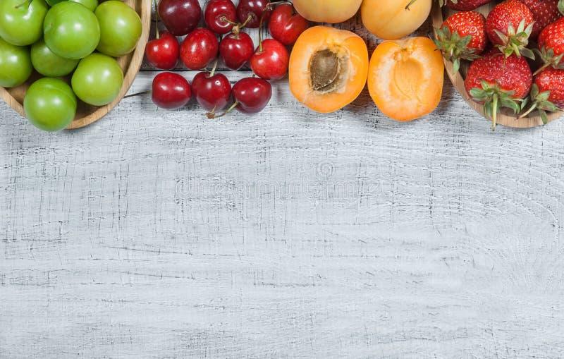 Sommarfrukter, gr?n plommon, r?d k?rsb?r, jordgubbe, aprikos p? vit tr?bakgrund arkivbild