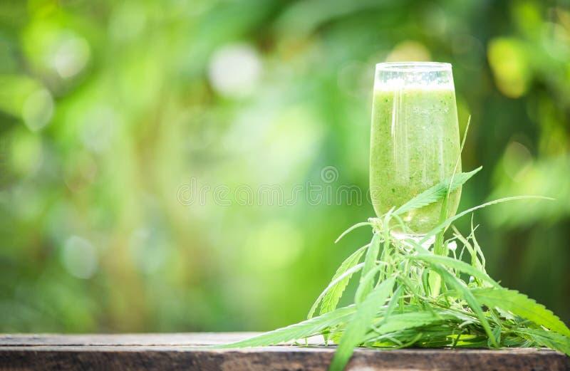 Sommarfruktsaft med gröna fruktsmoothies i exponeringsglas med växten för cannabisbladmarijuana på trätabellgräsplanbakgrund - ca arkivbild
