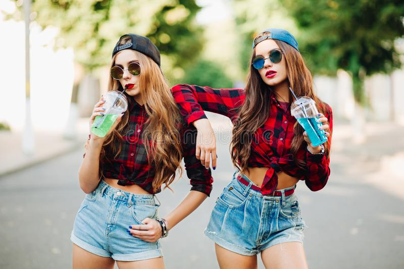 Sommargataflickor, två flickor på gatan, systrar, två härliga flickor går runt om stad fashionably och stylishly arkivfoton